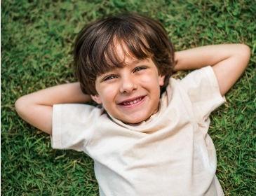 Contato com a natureza melhora desenvolvimento intelectual das crianças; imagem mostra menino deitado na grama sorridente