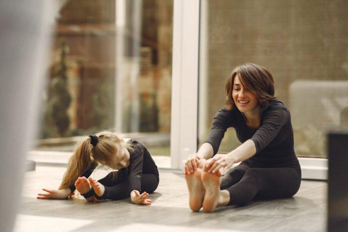 Imagem mostra mãe e filha fazendo alongamento sentadas no chão para ilustrar matéria sobre como manter a rotina de exercícios das crianças na quarentena.