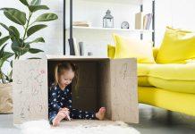 Criança brinca dentro de caixa de papelão toda rabiscada. Criar um lugar em casa que a criança possa ir para se acalmar é uma das dicas da Disciplina Positiva que ajudam na autorregulação e no autocontrole.