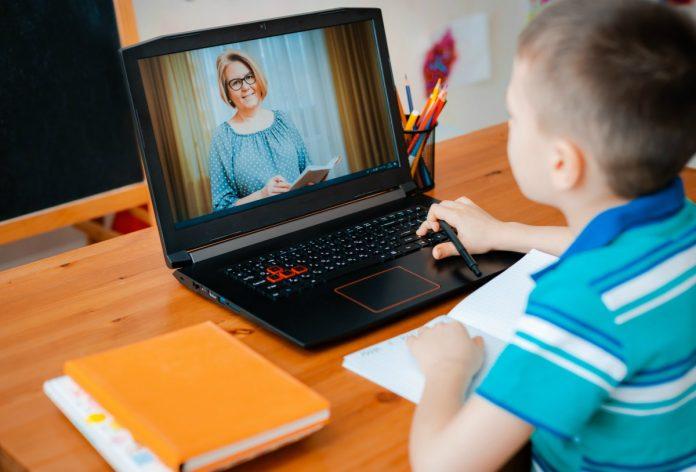 Menino de camisa azul listrada assiste a aula no computador. A improvisação do ensino imposta pela quarentena pode interferir na saúde mental e emocional das crianças.