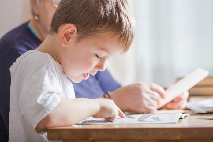 Criança em processo de alfabetização, está sentada e lê algo na mesa com o dedo acompanhando as letras. Ao fundo, um adulto aparece um adulto a seu lado.