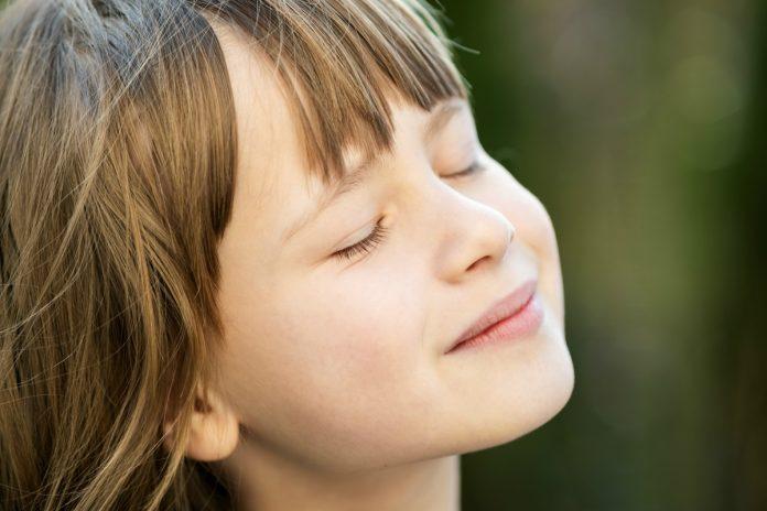 Ensinar a criança a respirar, como nesta foto em que o menino respira de olhos fechados, favorece aspectos como controle das emoções, capacidade de atenção e foco