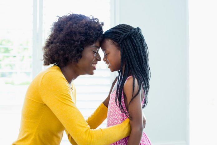 Estilo de parentalidade dos pais define características dos filhos na vida adulta. Na foto, mãe e filha negras se olham de bem perto, com as testas encostadas uma na outra.