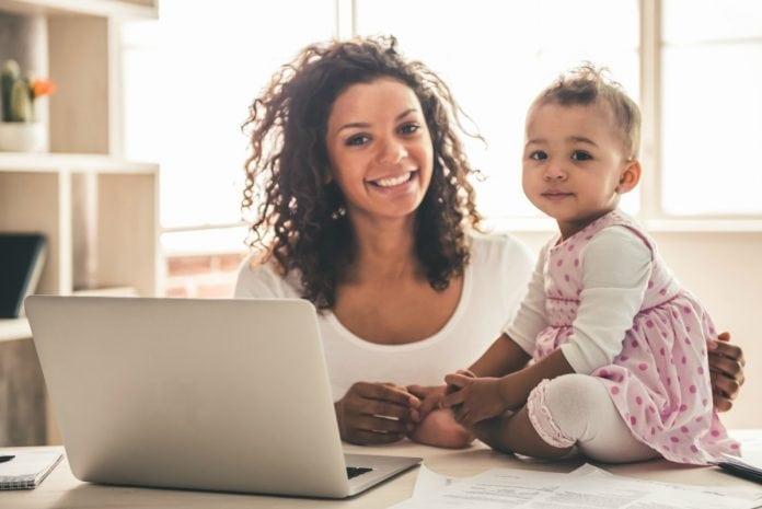 Desenvolvimento da criança pode ser estimulado por meio de ações simples como a conversa e brincadeiras. Nesta imagem, mãe negra parece estar brincando com a sua bebê.