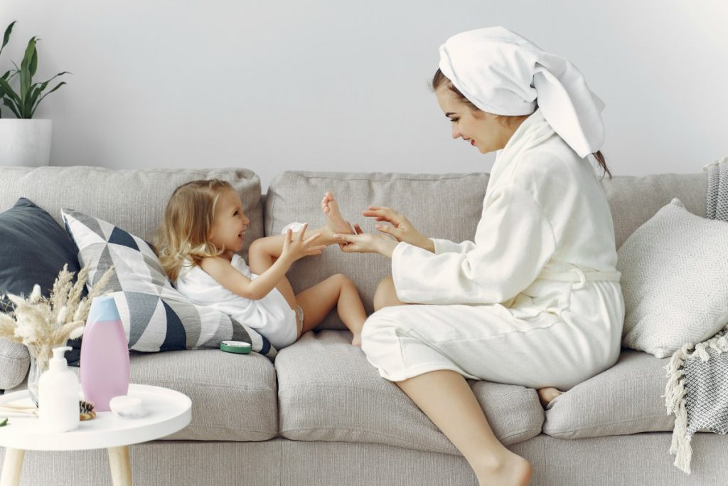 Mãe de roupão e toalha na cabeça está no sofá com a filha e passa creme no pé dela. Hidratar a pele e as mão das crianças é essencial para evitar o ressecamento diante das lavagens com sabonete e o uso de álcool gel em excesso que evitam o contágio com o coronavírus.