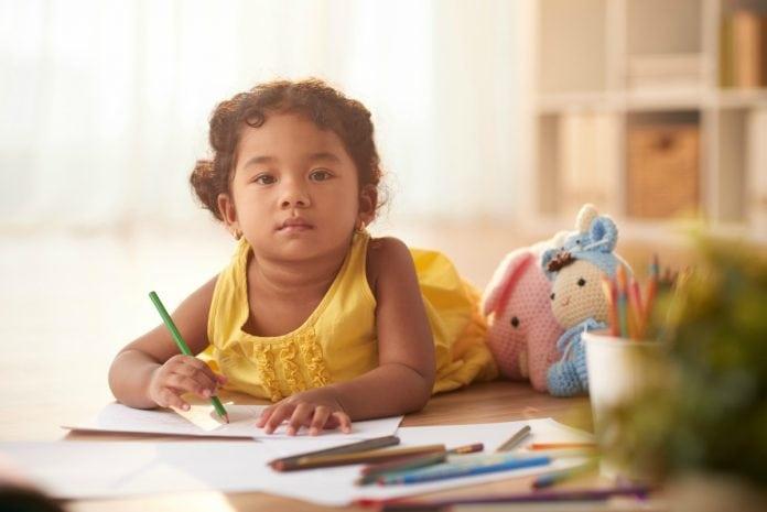 Pais cogitam tirar seus filhos das escolas infantis, mas especialistas ressaltam importância de ações pedagógicas como mostra esta foto, em que uma menina morena pequena desenha deitada no chão.