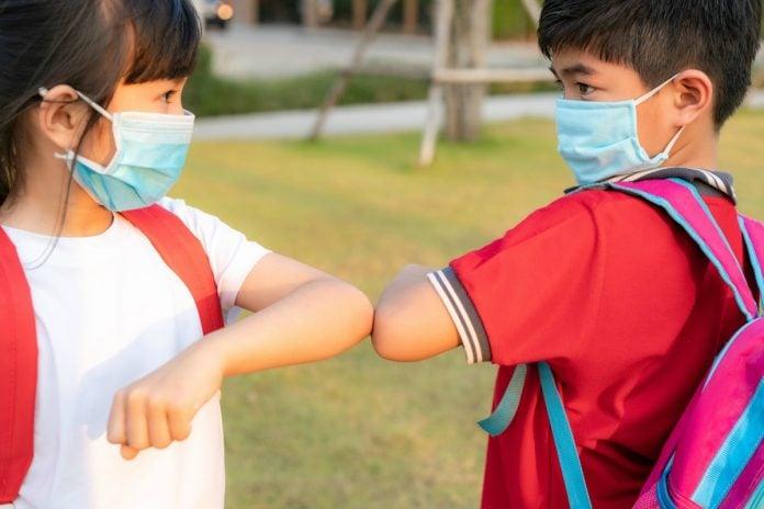 SBP divulga documento com orientações para volta às aulas nas escolas: crianças terão de manter distanciamento, como nesta imagem, em que aparecem um menino e uma menina asiáticos se cumprimentando com os cotovelos.