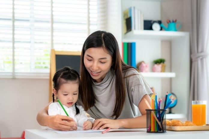 Mãe ajuda a filha em atividades de ensino remoto, já que a criança está estudando longe da escola.