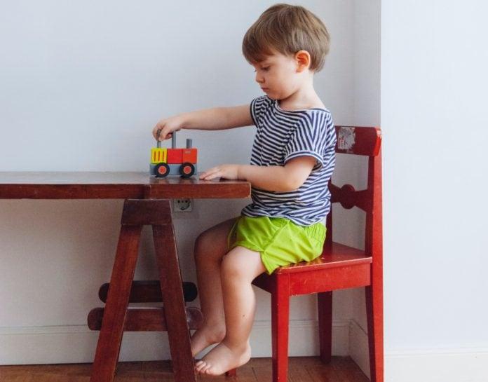 Criança brinca sozinha com carrinho em uma mesa, ilustrando matéria sobre com quem pais vão deixar as crianças para voltarem a ir ao trabalho.