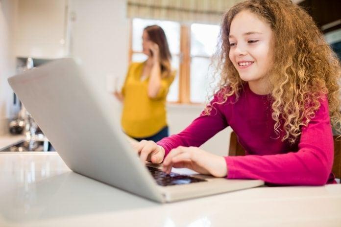 Criança usa o computador enquanto mãe está ao fundo; imagem ilustra matéria sobre acesso de crianças e adolescentes à internet.