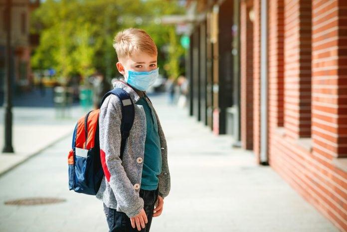 Criança usando mochila e máscara em ilustração à matéria sobre as medidas divulgadas para a reabertura das escolas.