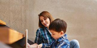 Mãe e filho olham computador, ilustrando matéria sobre projeto do CCBB que oferece atividades para crianças e adultos.