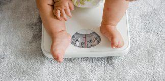 Bebê está em cima de balança para ilustrar matéria que fala sobre ligação entre dormir tarde e sobrepeso.
