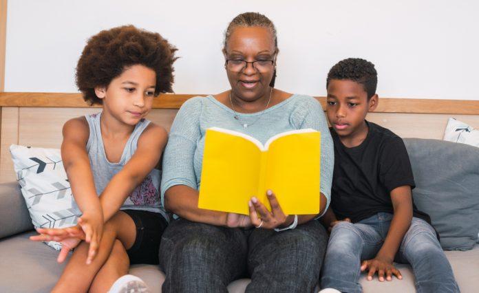 Mulher conta história para duas crianças; imagem ilustra matéria sobre live que vai abordar os benefícios da contação de histórias para as crianças.