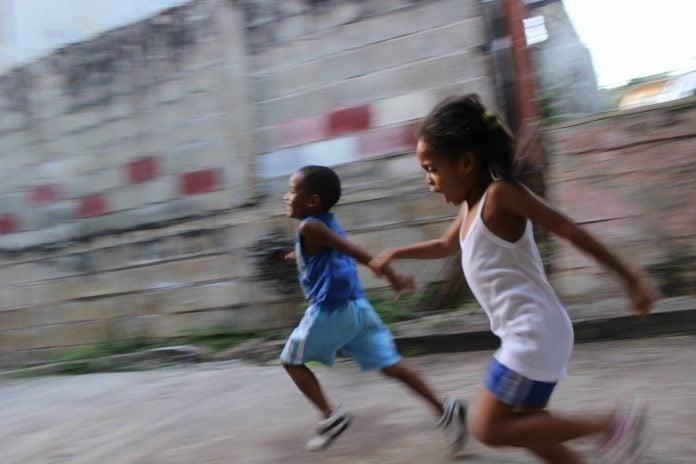 Escolas de concreto, que poderiam ser como essa imagem – em que duas crianças negras correm em um piso de cimento com uma parede ao fundo acimentada também – não incentivam o brincar e o cuidar