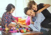 Dicas da Disciplina Positiva para dias mais harmoniosos na quarentena, como essa família da imagem, em que a mãe recebe massagem do filho enquanto brinca com a filha