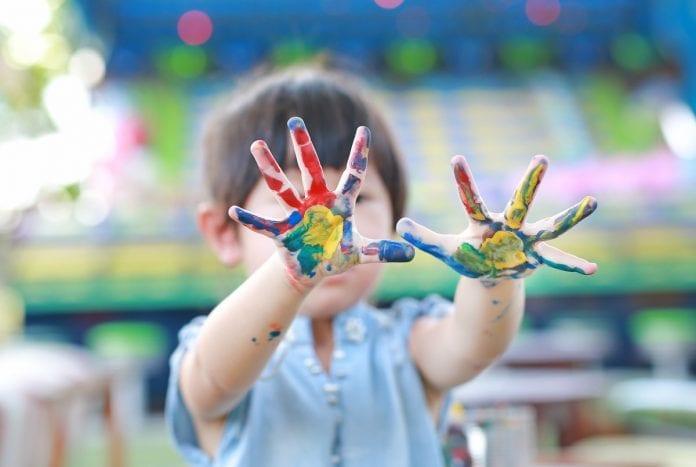Retomada das aulas presenciais: o que pesa a favor das crianças pequenas, como esta da imagem que mostra as mãos sujas de tinta