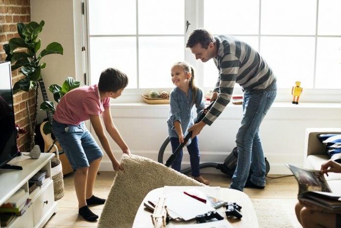 Filhos responsáveis devem aprender com os pais a ajudar nas tarefas da casa, como nessa imagem que os dois irmãos ajudam o pai a limpar a sala