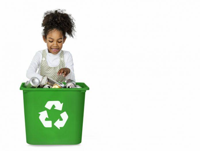 Consumo consciente: separar o lixo corretamente, como nesta imagem em que criança negra olha para lixeira somente com latas, é uma das ações que que os pais podem ensinar para as crianças para reduzir os impactos ao planeta
