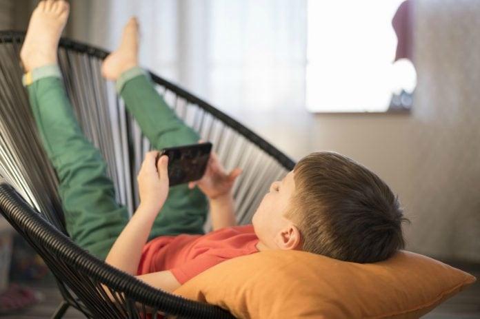 Tempo dedicado às telas, como o garoto desta imagem que assiste algo pelo celular deitado em uma cadeira, é alvo de mais um alerta da Sociedade Brasileira de Pediatria