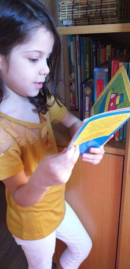 Estela, 5 anos, filha da personal organizer Cris Catussato, retira um livro da estante que fica à sua altura