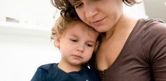 Regressões no desenvolvimento da criança são comuns frente a situações atípicas, como esta de pandemia, e aos pais cabe acolher os filhos e conversar com eles, como nesta foto em que garoto está sentado no colo da mãe, e esta encosta sua cabeça na dele