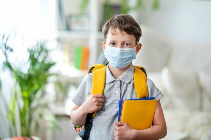 O retorno das aulas presenciais nas escolas devem ser retomadas em setembro, seguindo uma série de protocolos como o uso de máscara, conforme mostra garoto nesta imagem