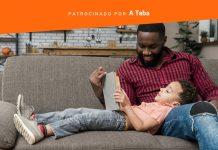 Pai lê com seu filho no sofá