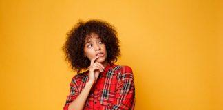 Autoconfiança nos faz sentir mais seguras; na imagem mulher negra está com a mão sob a boca e olha para o lado com cara de dúvida