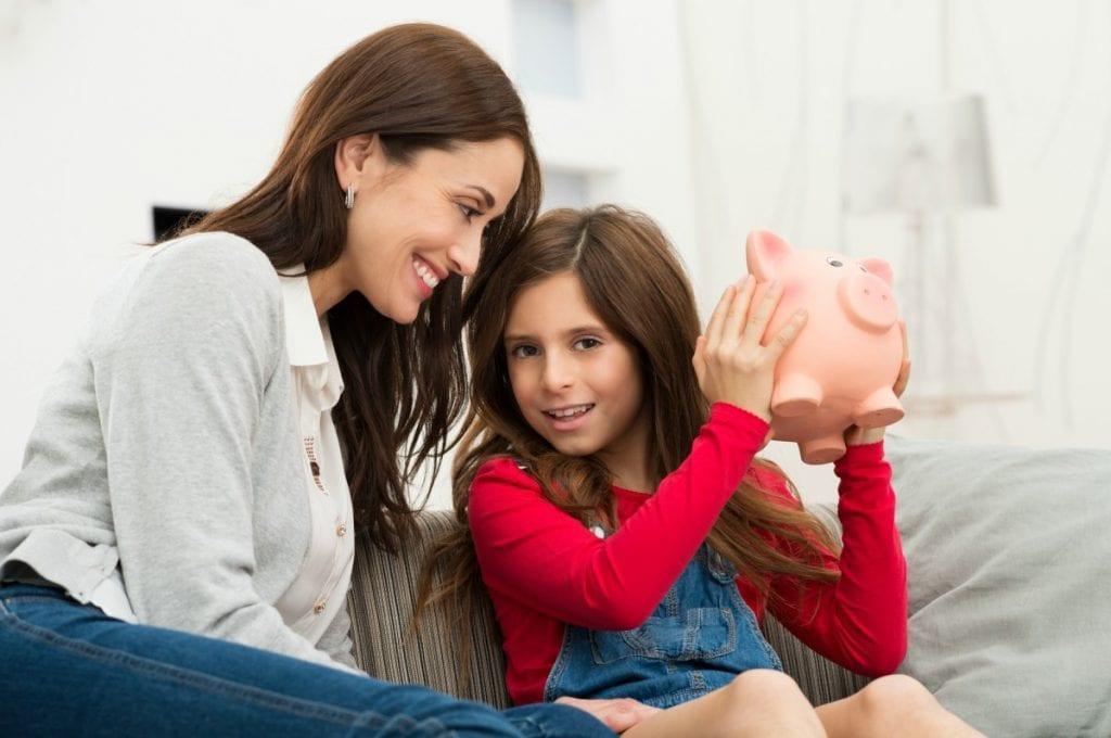 Dar mesada à criança, como garota da imagem que segura cofrinho junto à mãe, a ensina a lidar com conceitos importantes da sua vida financeira, entre os quais, a definição de orçamentos para os gastos.