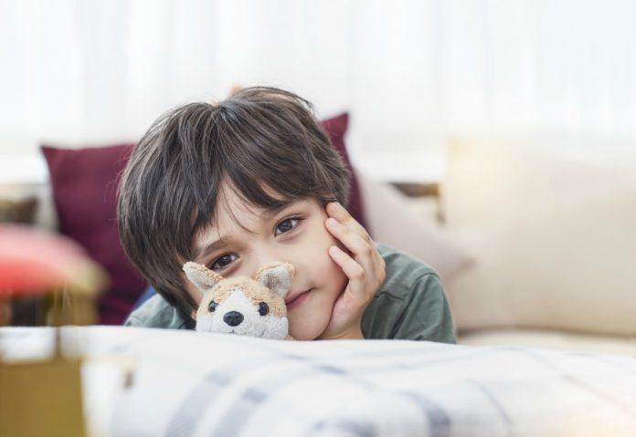 Capacidade empreendedora da criança é cristalina; na imagem, garoto está deitando na cama de bruços com a cabeça levantada e a mão no queixo, pensativo