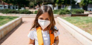 Surtos de covid-19 em escolas são registrados em alguns países, diz OMS; na imagem, garota com mochila nas costas e máscara olha para a câmera