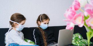 Pais poderão optar por não mandar os filhos à escola; na imagem, duas meninas de máscara estão no sofá com um computador sob o colo de uma delas