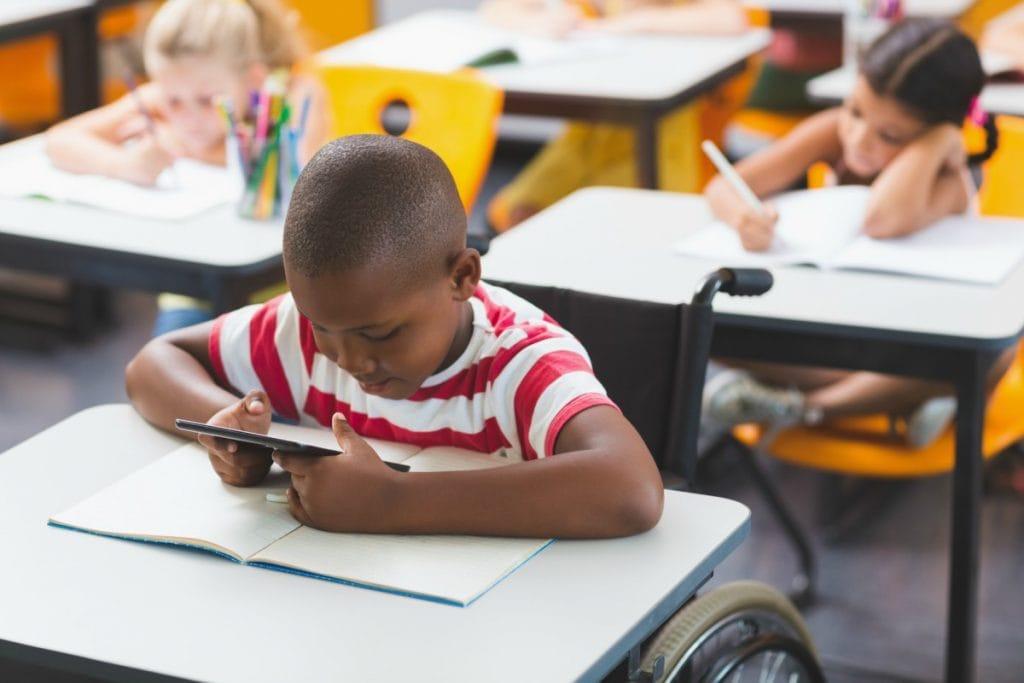 Estudantes com deficiência sem comorbidades podem voltar às aulas quando as escolas reabrirem; na imagem garoto negro e cadeirante está em sala de aula junto com outros alunos olhando tablet sobre a mesa