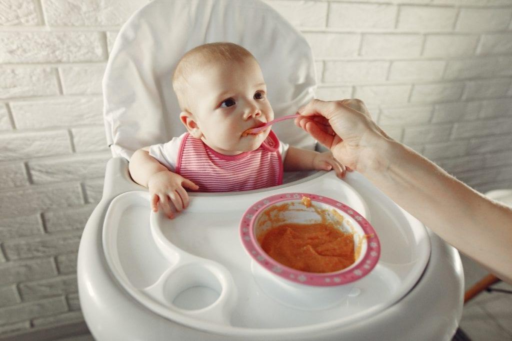 Bebê sentado no cadeirão, sendo alimentado com papinha; imagem ilustra matéria sobre papinhas orgânicas.