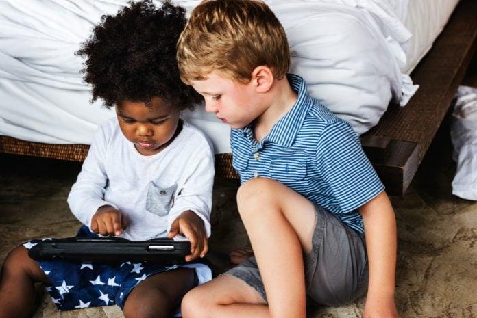 Duas crianças brincando com tablet, em ilustração à matéria sobre uso de telas.