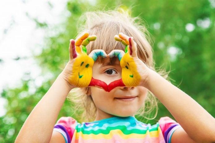 É preciso estimular as crianças a se tornarem empreendedoras; imagem mostra menina que faz um coração com as mãos que estão pintadas coloridas