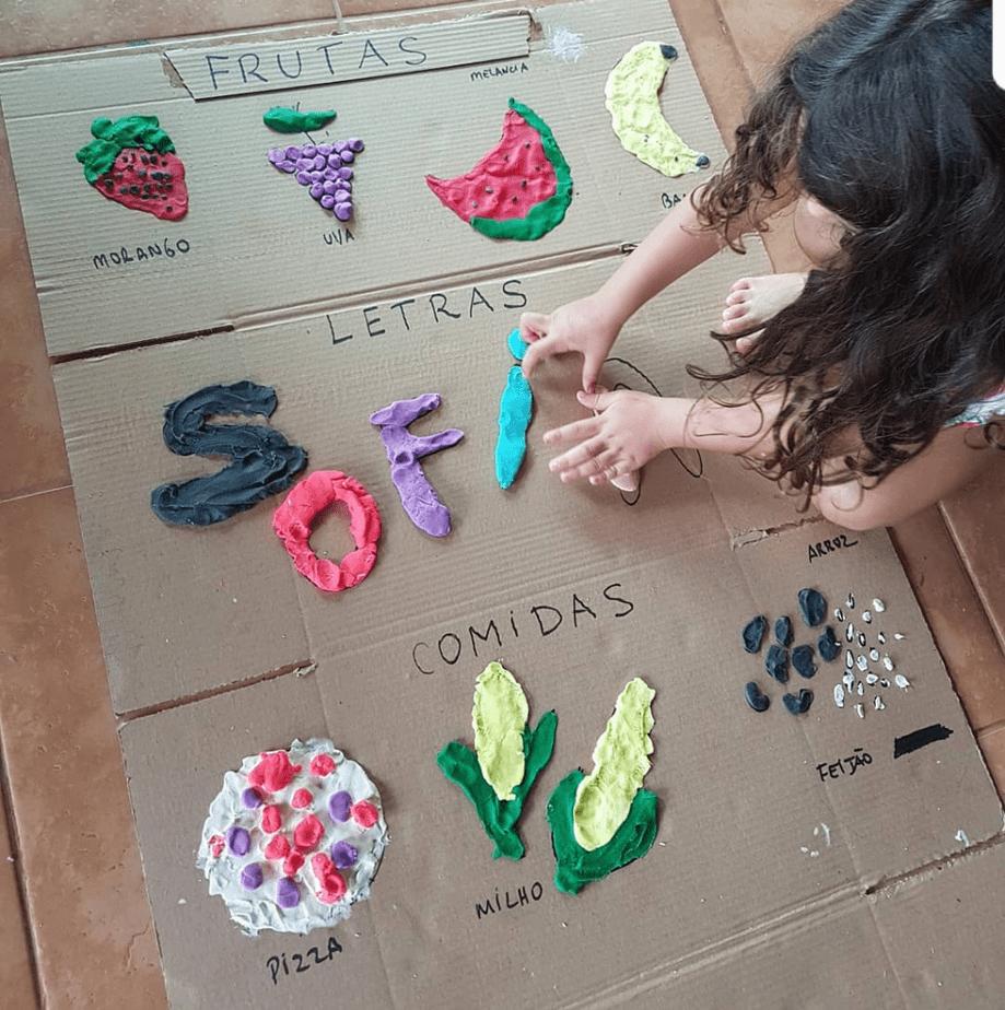 Brincadeiras com massinha; imagem mostra garota brincando com as massinhas em caixa de papelão que tem desenho de frutas e legumes