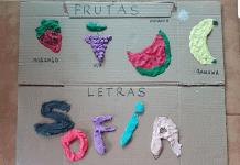 Brincadeiras com massinha: desenhando frutas na caixa de papelão; imagem mostra papelão com frutas e legumes desenhados e a massinha colorida por cima deles, no meio, nome Sofia escrito e coberto de massinha