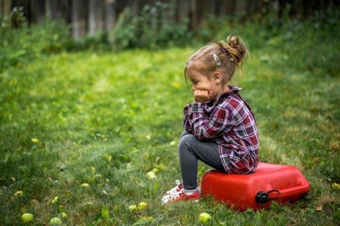 Crianças sensíveis se adaptam bem às restrições da pandemia; na imagem, garota sentada em brinquedo sob a grama apoia queixo sobre o braço e olha para a frente