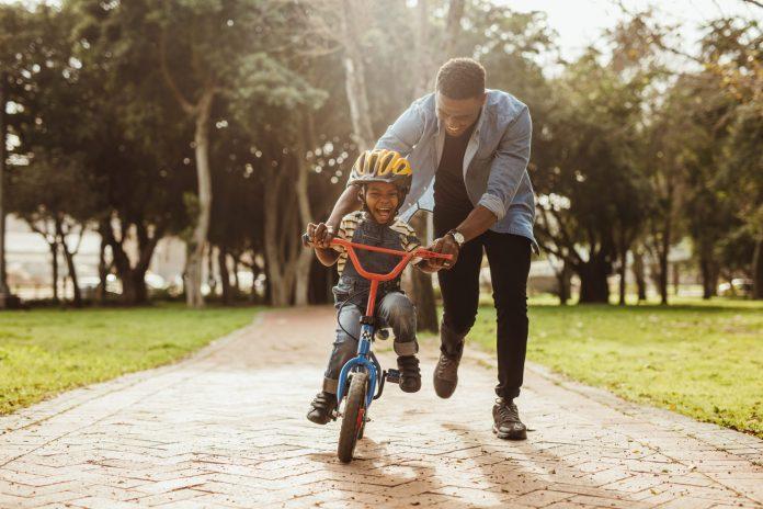 Papel dos pais na criação dos filhos é essencial e traz benefícios aos próprios pais, na imagem pai ajuda o filho a andar de bicicleta
