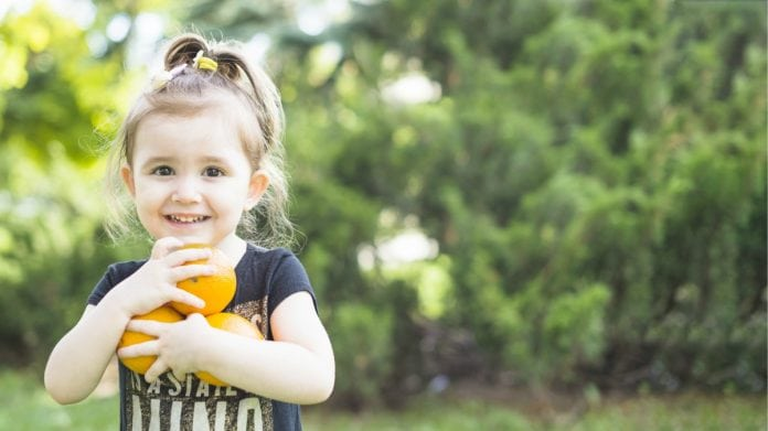 Frutas de época como as laranjas que a garota segura abraçando-as nesta foto, são mais baratas e possuem menos agrotóxicos