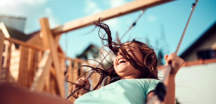 Impacto da pandemia nas crianças: elas levarão marcas deste período?; imagem mostra garota sorridente em balanço ao ar livre