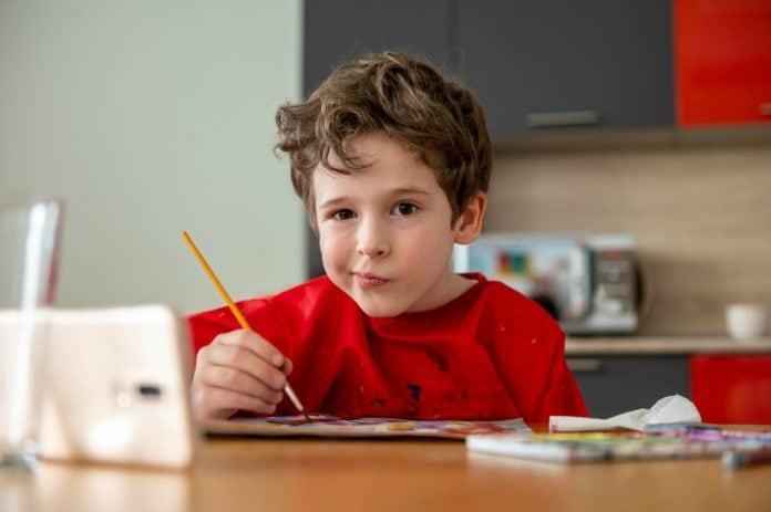 Aulas online e maternidade atípica; na imagem, menino de blusa vermelha pinta algo em frente a um tablet e faz bico com a boca para o lado