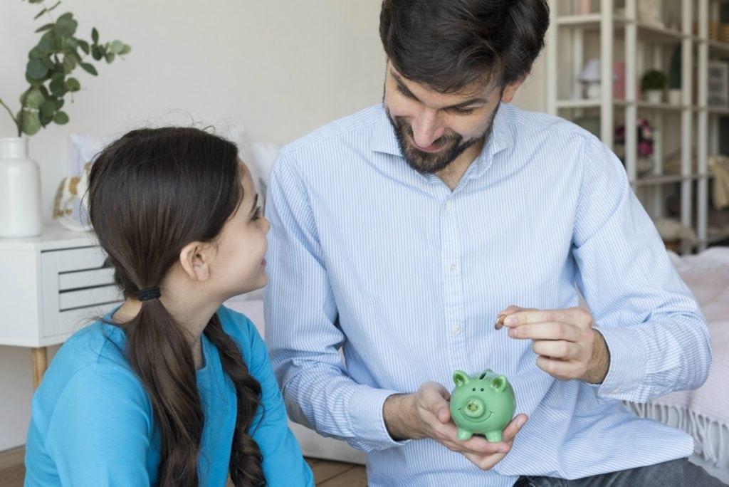 Se a criança descumpre o combinado, terá desconto no valor da mesada?; na imagem, pai coloca moeda em cofrinho e olha para criança que está ao seu lado