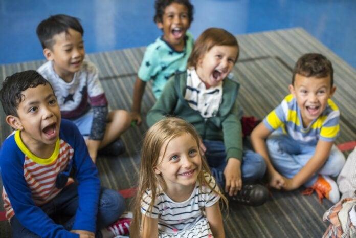 A educação de qualidade está chegando a todos?; imagem mostra 6 crianças em idade pré-escolar olhando para a frente e o alto, algumas de boca aberta gritando