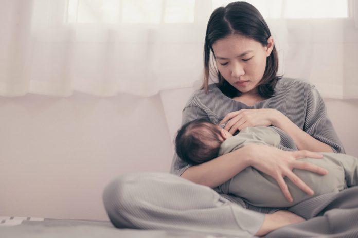 Baby blues, depressão pós-parto, a pandemia e o papel do pediatra; na imagem, mãe de traços orientais amamenta o seu bebê