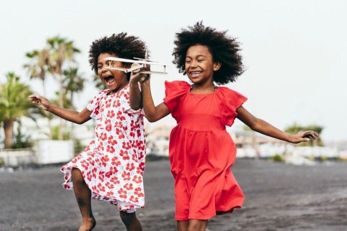 Em defesa da infância, devemos voltar para a escola, diz a pediatra Talita Rizzini; imagem mostra duas garotas negras correndo felizes, uma de vestido vermelho e a outra de vestido branco com estampas vermelhas