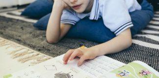 Dia da alfabetização: mais da metade das crianças não sabe ler; na imagem, menino passa dedo sobre letras em livro