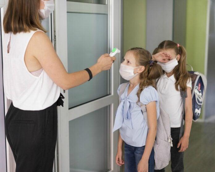 Volta às escolas em SP: 3 diretoras opinam sobre retorno em outubro; imagem mostra mulher medindo temperatura de aluna com máscara, atrás dela há outra aluna com máscara e mochila